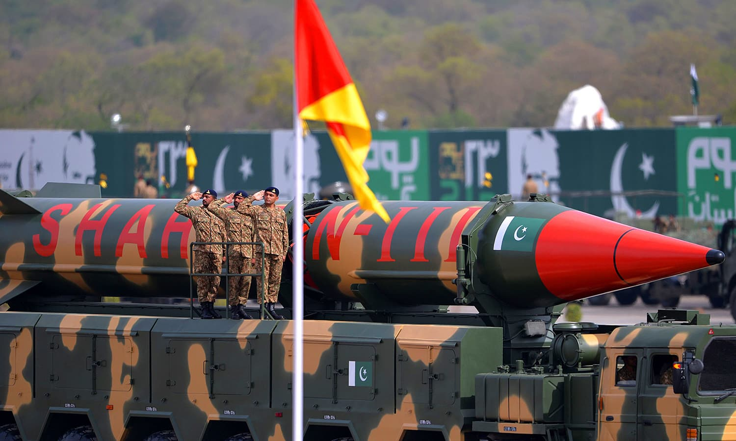 Army soldiers salute as they travel on a vehicle carrying long-range ballistic missile Shaheen III during the Pakistan Day military parade. ─ AFP