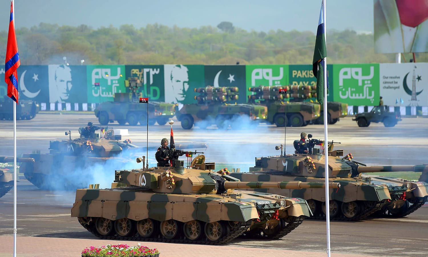 Military personnel ride on Al-Khalid tanks during the military parade. ─ AFP