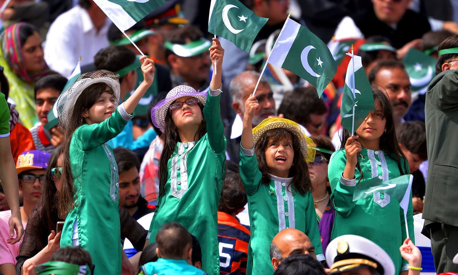 Young children wave flags as they watch the Pakistan Day military parade. ─ AFP