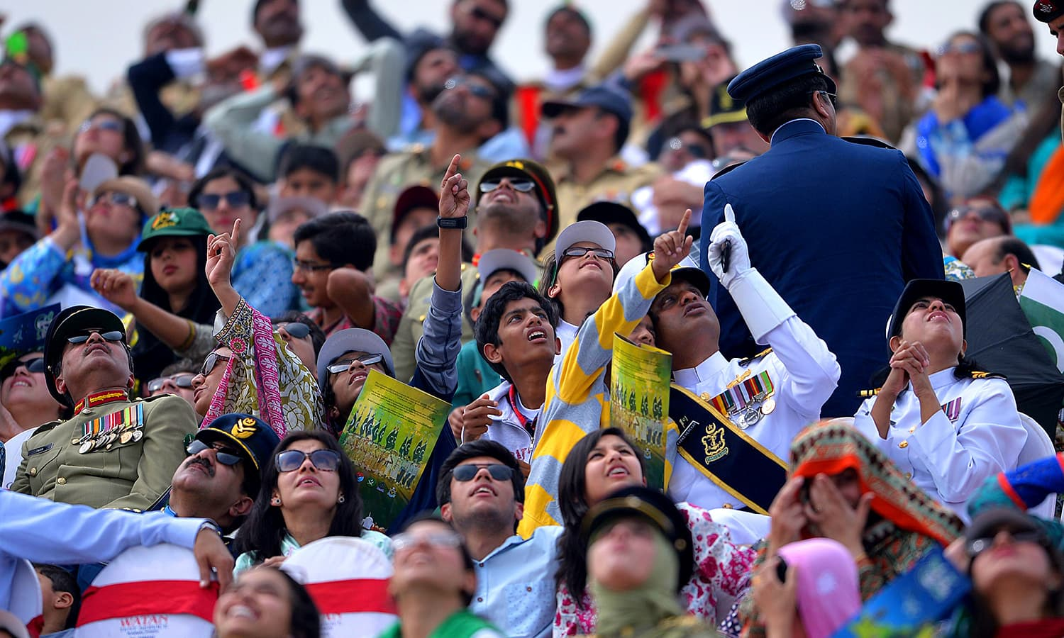 Spectators watch the performance of an F-16 fighter jet during the Pakistan Day military parade. ─ AFP