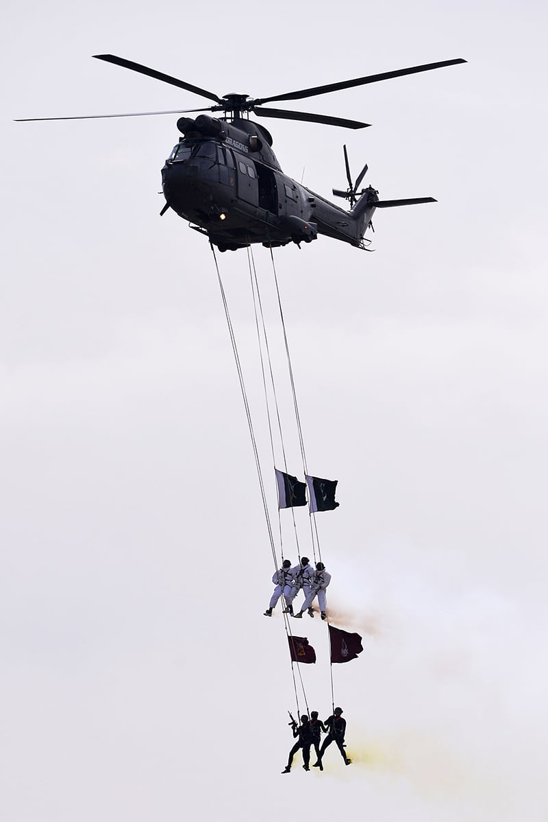 SSS commandos hang from a helicopter performing a fly-past during the Pakistan Day military parade. -AFP