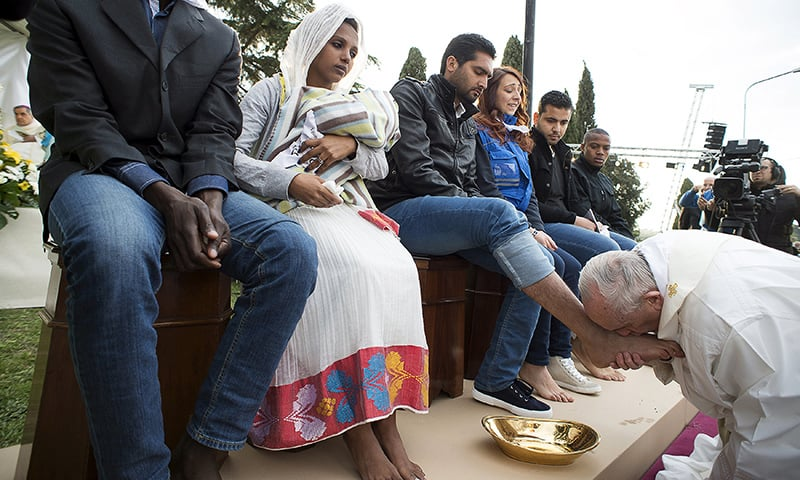 Pope washes feet of Muslim migrants, says 'we are brothers'