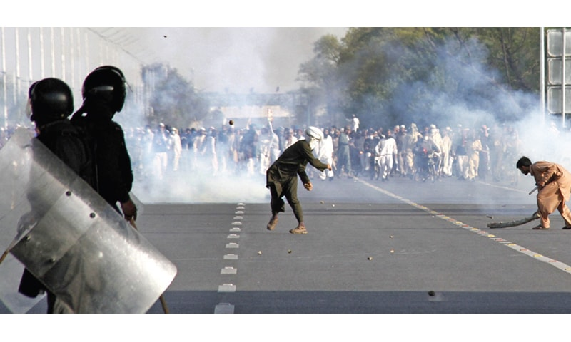Protesters hurl stones at law enforcement personnel on Islamabad Expressway, as another sweeps away a teargas canister. — Photo by Tanveer Shahzad