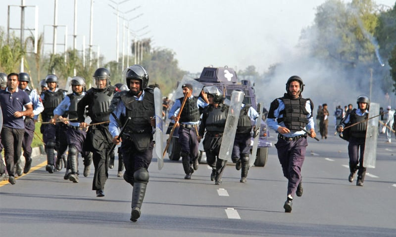 Policemen retreat from the protesters. — White Star