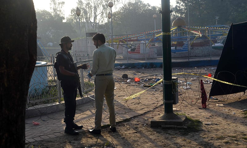 A police commando (L) speaks with a forensics expert at the site of the March 27 suicide bombing, in Lahore.─AFP