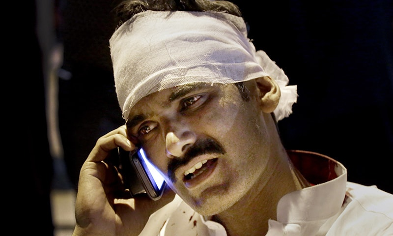 An injured man from the bomb blast talks on his cell phone at a local hospital in Lahore.─AP