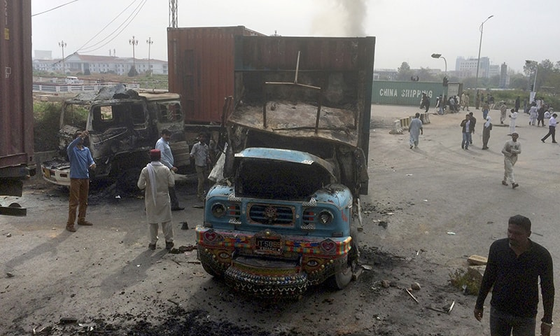 People look at trucks burnt by supporters of Sunni Tehreek during a march toward the parliament.─AP