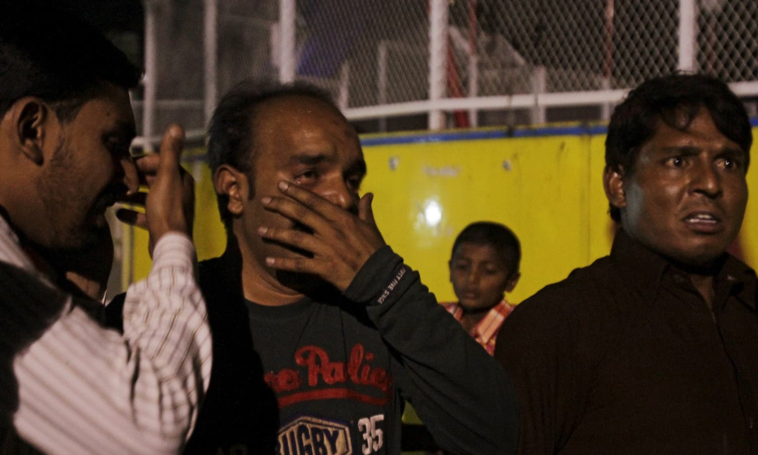 Men mourn the death of their relatives after the blast outside a public park in Lahore.─Reuters