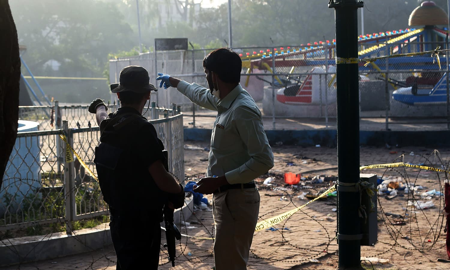 Security officials examine the cordoned-off site of the March 27 suicide bombing, in Lahore on March 28, 2016.─AP
