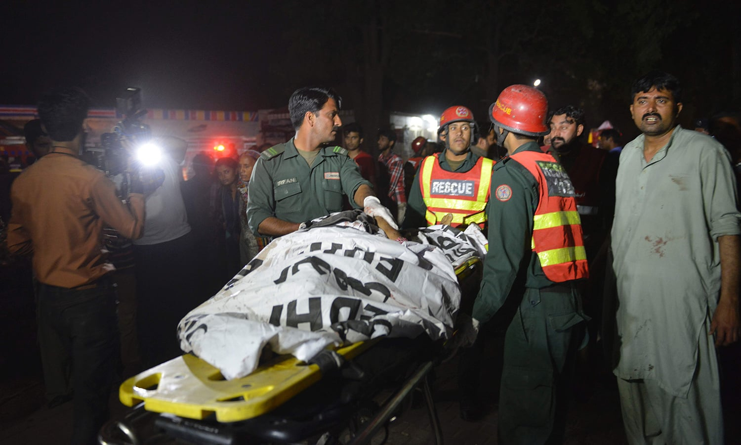Rescuers use a stretcher to shift a body from a bomb blast site.─AFP