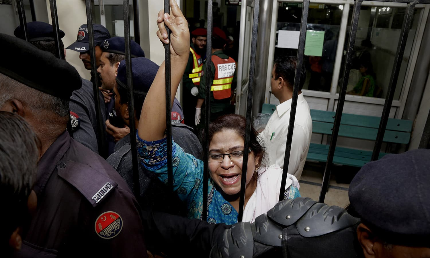 A woman weeps for her injured family members as she tries to speak to security at a local hospital in Lahore.─AP