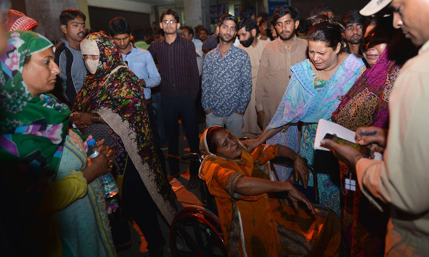 Relatives of injured victims gather outside the hospital in Lahore.─AFP