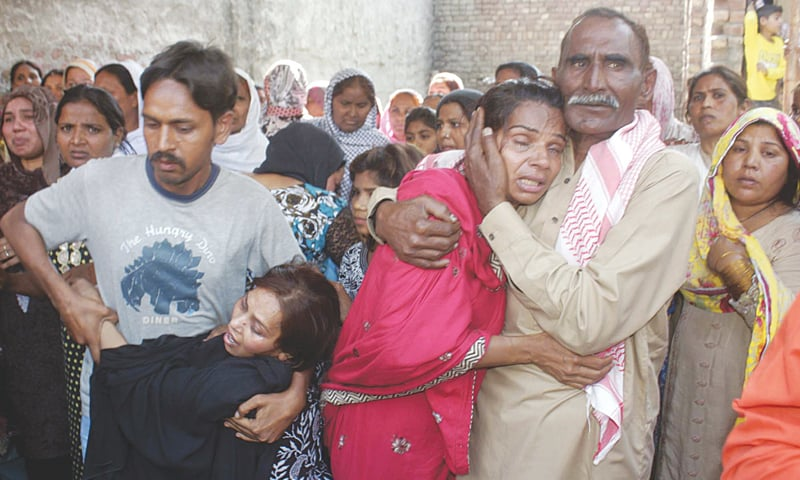 LAHORE: Grief-stricken relatives of a victim of Sunday's attack pictured at the funeral in Youhannabad on Monday.—PPI