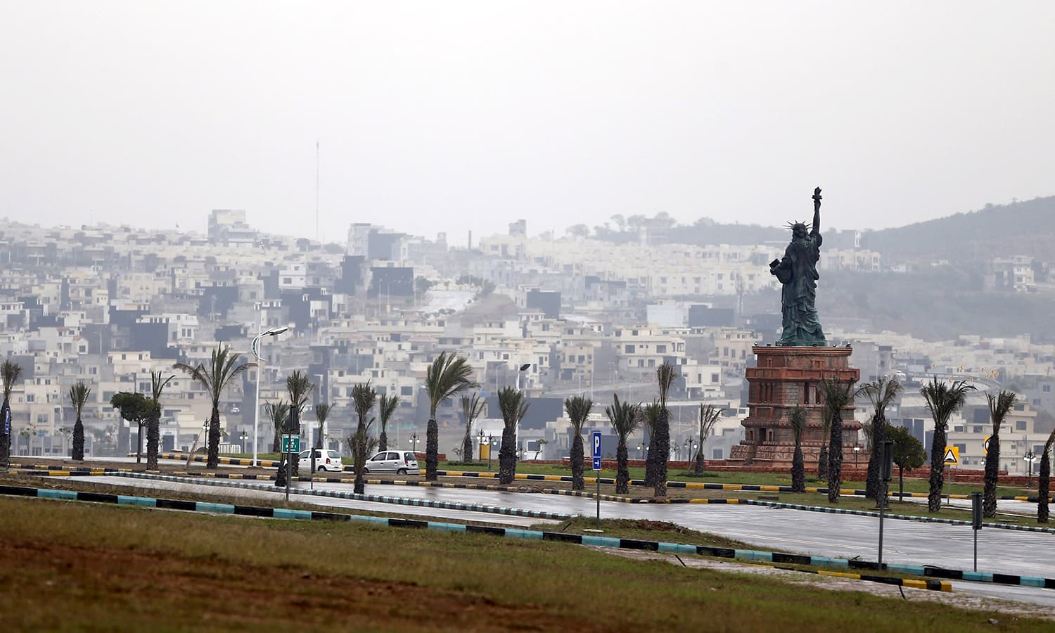 A replica of the Statue of Liberty stands on a hill overlooking the construction of new homes in Bahria Town on the outskirts of Islamabad.─Reuters
