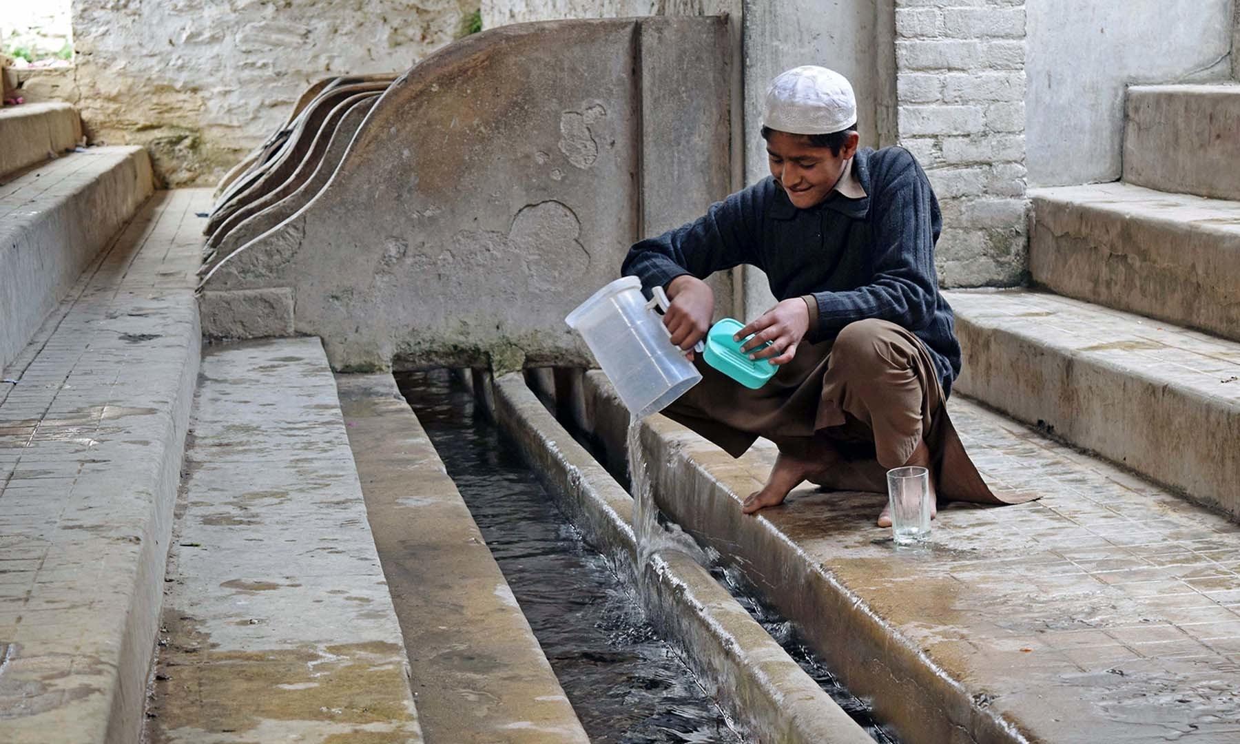 ایک بچہ سیدو بابا چشمے سے پانی بھر رہا ہے— فوٹو امجد علی سحاب