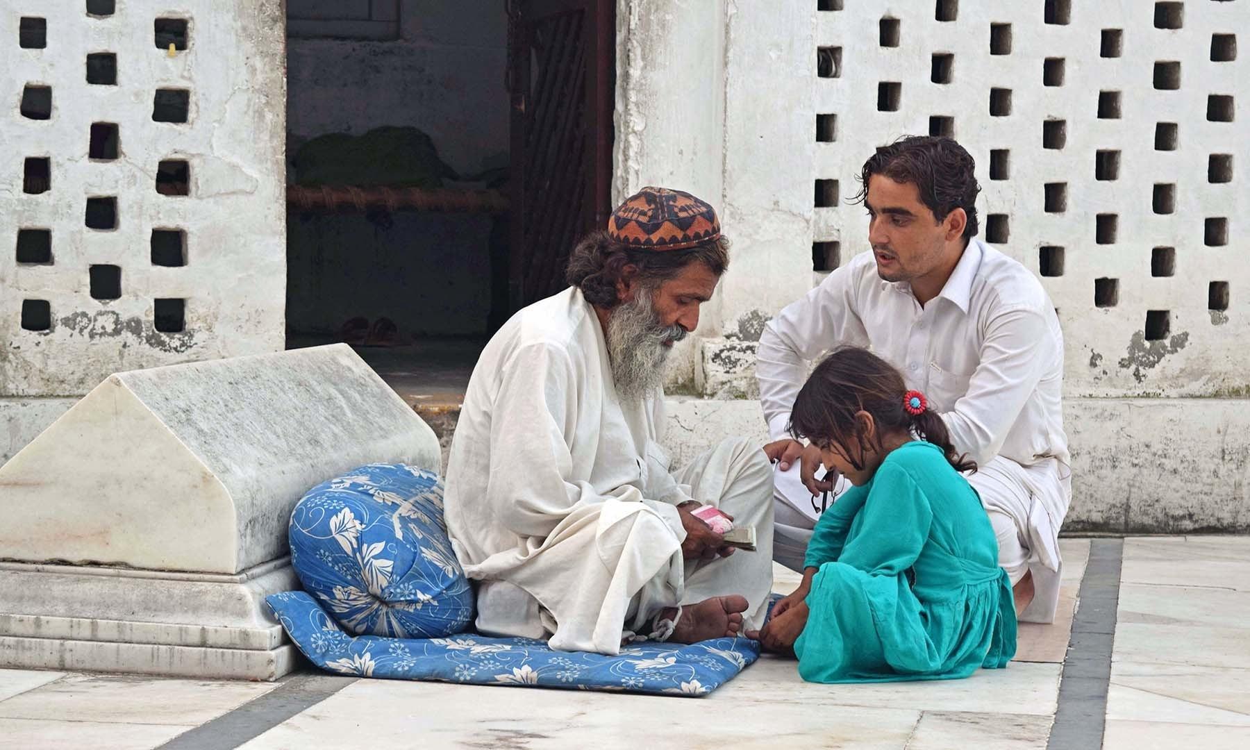 ایک ملنگ بیٹھا آنے والے زائر کی مشکل سن رہا ہے— فوٹو امجد علی سحاب