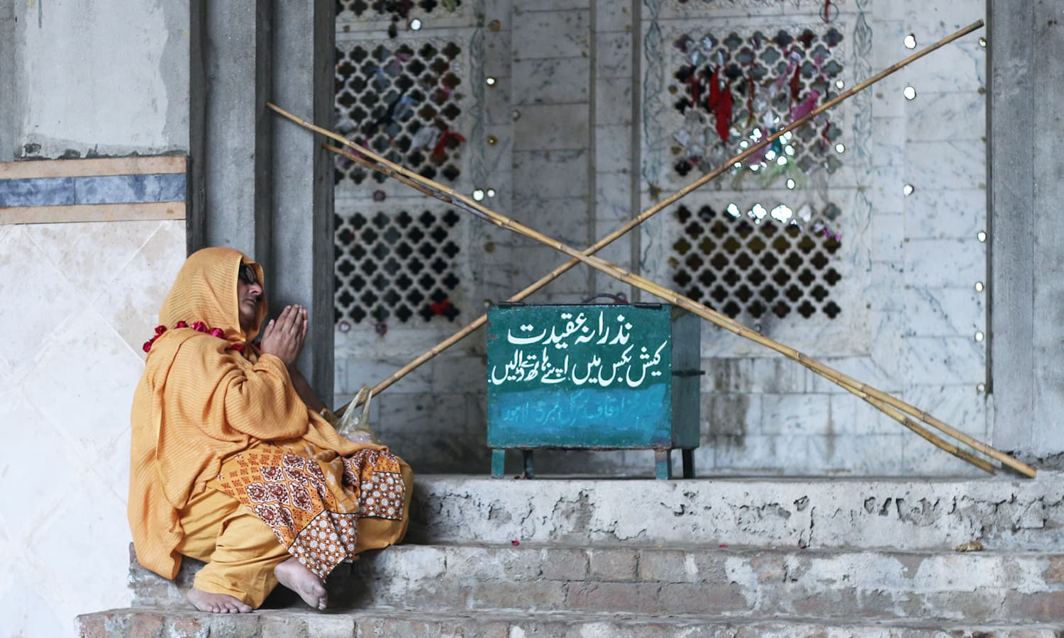 A woman sitting on the steps of the shrine of Sufi saint Madhu Lal Hussain.