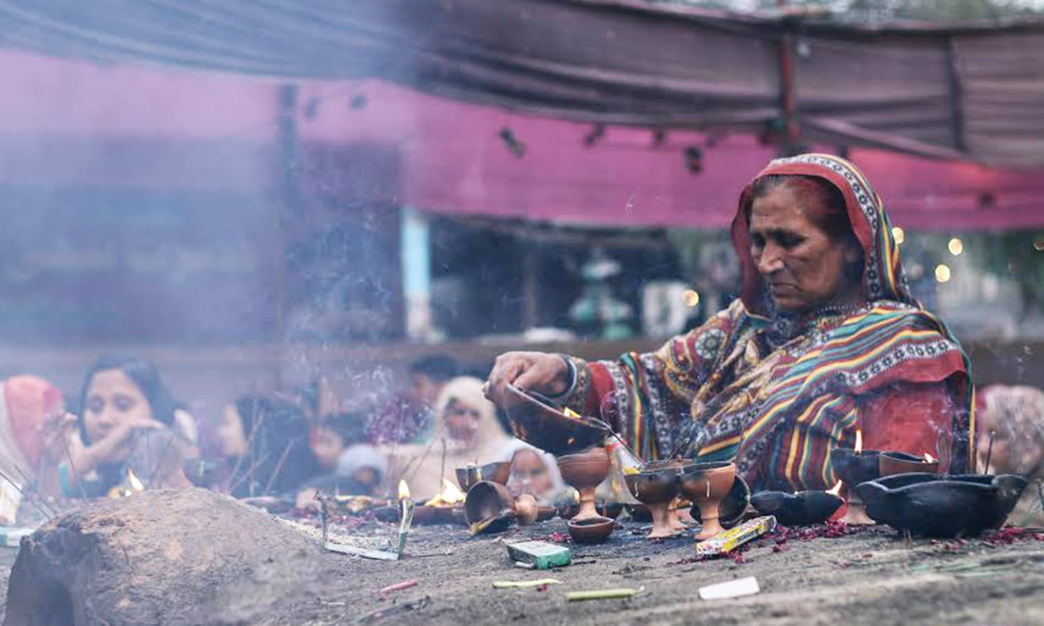 An old woman is pouring oil from a lamp which is considered a blessing.