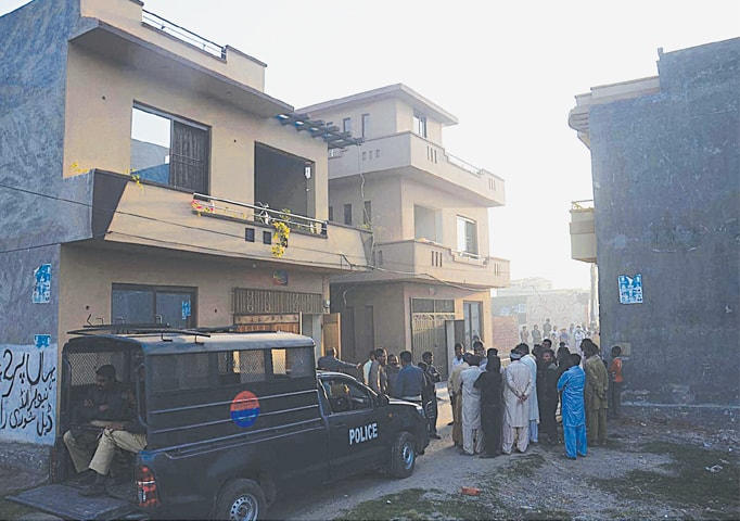 LAHORE: People gather at the site after a raid by CTD and police in an area on Raiwind Road. Five alleged militants were killed in the operation.—Online