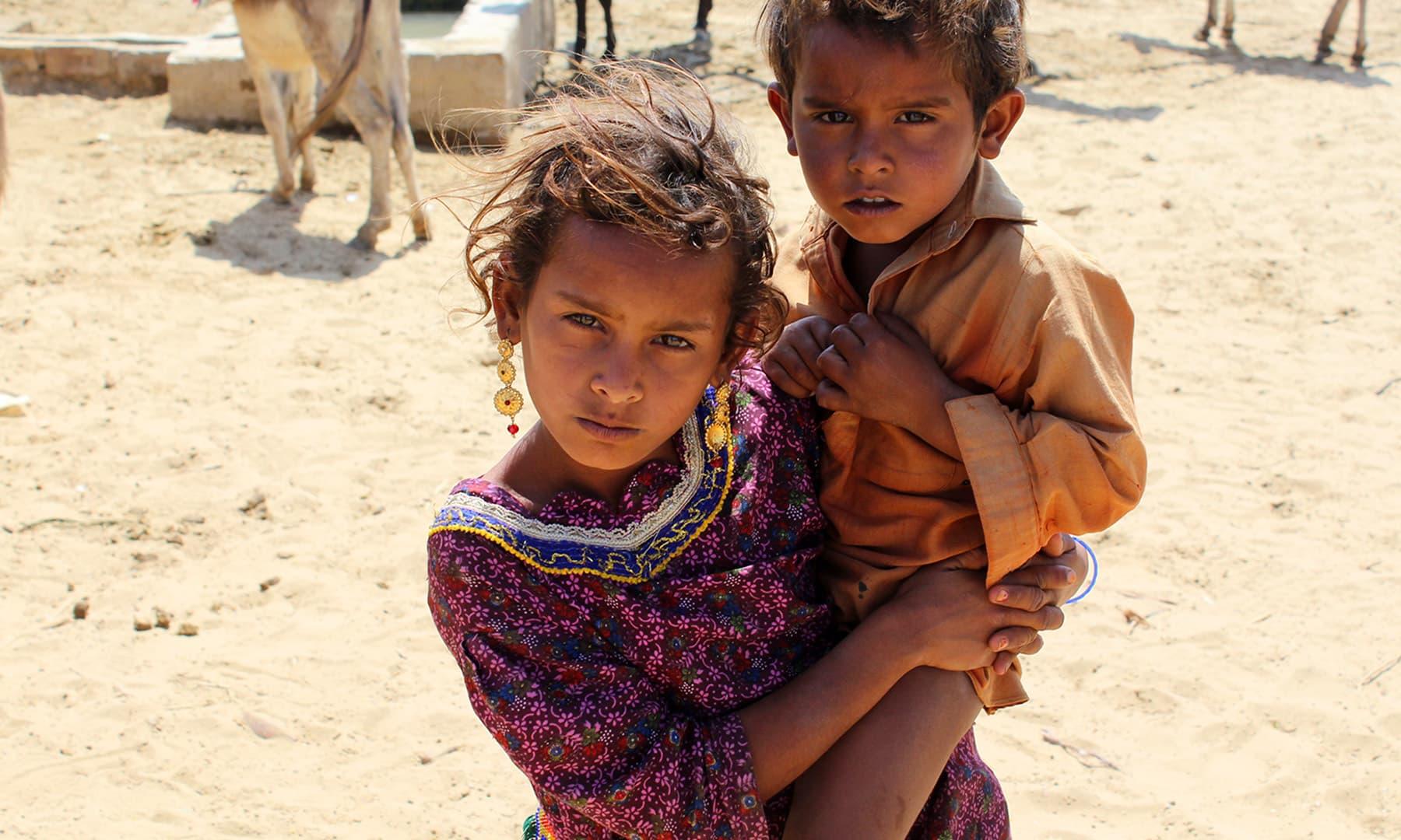 تھر میں چھوٹی بچیاں بھی گھر کی دیکھ بھال میں مدد کرتی ہیں۔— فوٹو اختر حفیظ۔
