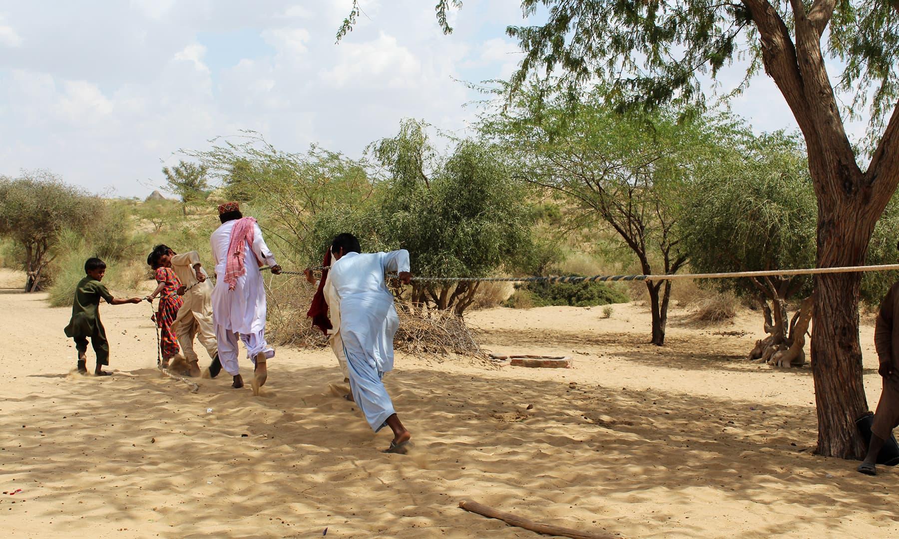تھر کے لوگ کنوئیں سے رسی کی مدد سے پانی نکال رہے ہیں۔— فوٹو اختر حفیظ۔