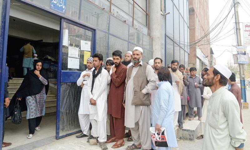 People line up outside the Nadra office in Peshawar. — Dawn