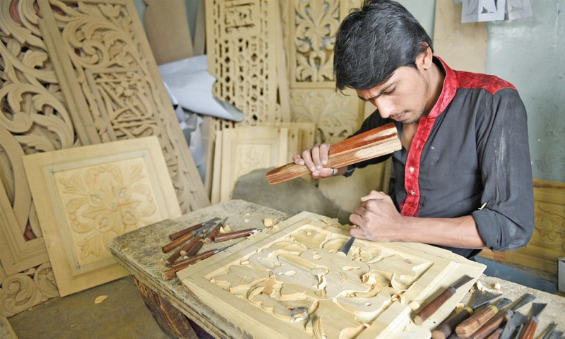 Fayyaz Ali chisels a wood panel at his workshop.