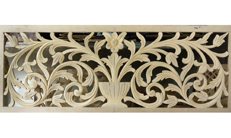 A floral pattern carved on wood. It is to be fixed on the main door of the house.