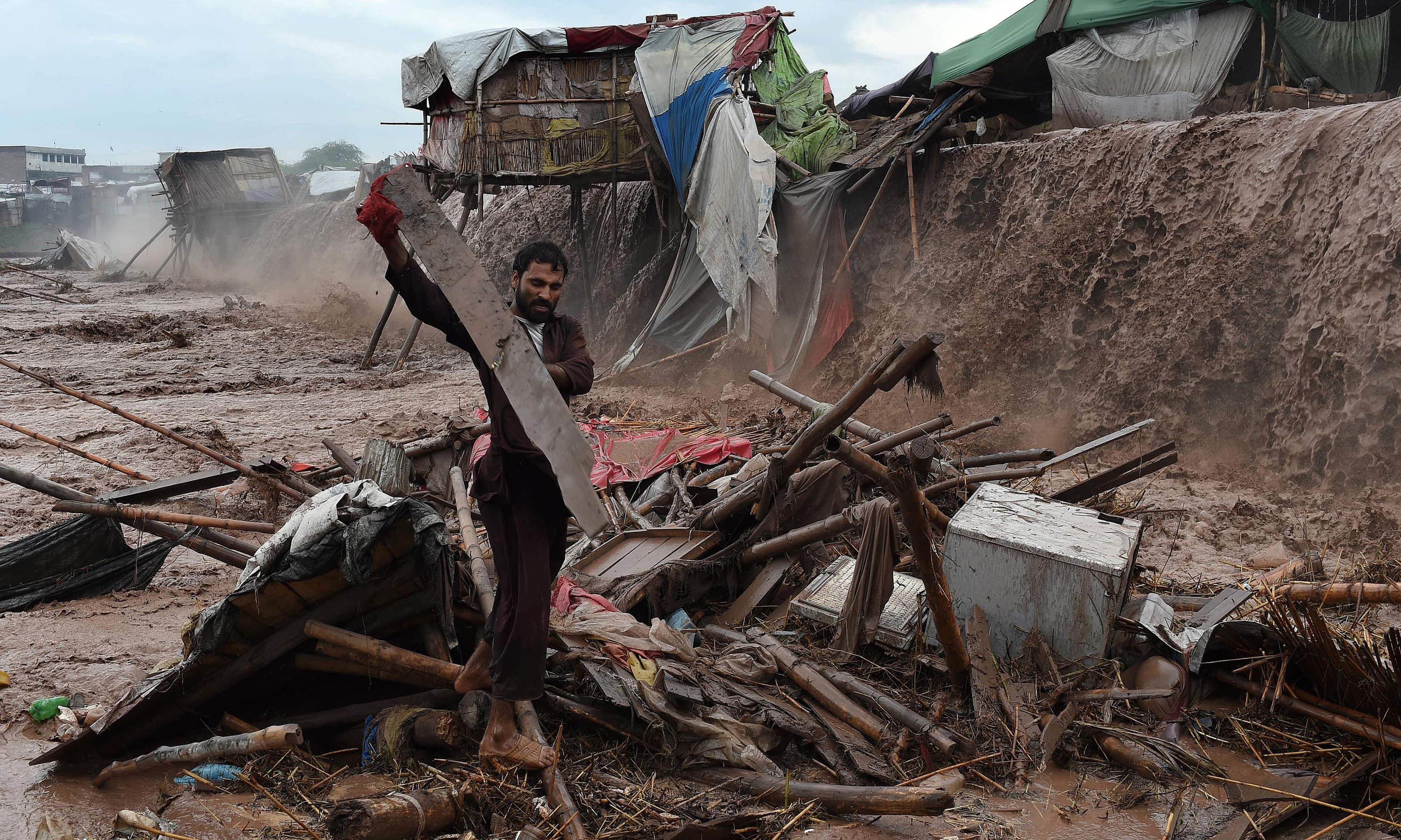 Flood waters rush through a market area as a man tries to salvage materials on the outskirts of Peshawar. AFP