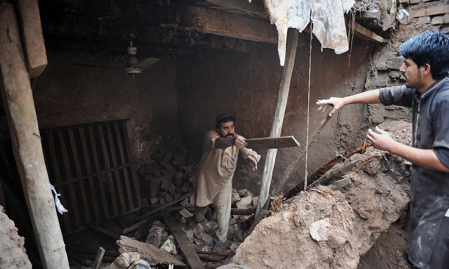 Residents remove debris from a damaged house after heavy rains caused devastation in the outskirts of Peshawar. —AFP