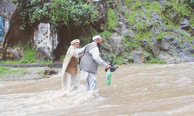 SHANGLA: A man helps an old man corss the river swollen by heavy rains in the area near Besham on the Karakoram Highway on Sunday.—Photo by Umar Bacha