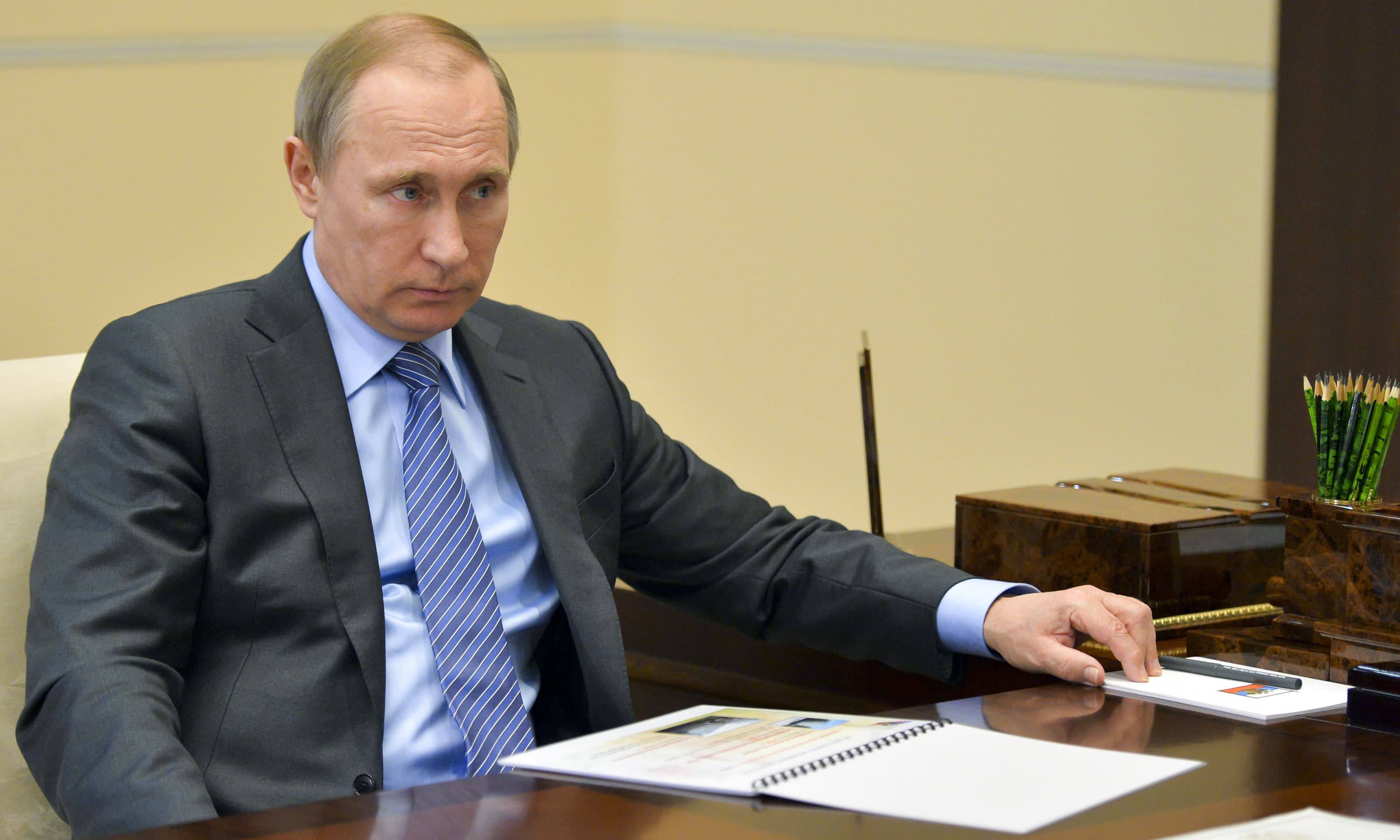 Putin listens during a meeting in the Novo-Ogaryov residence. —AP