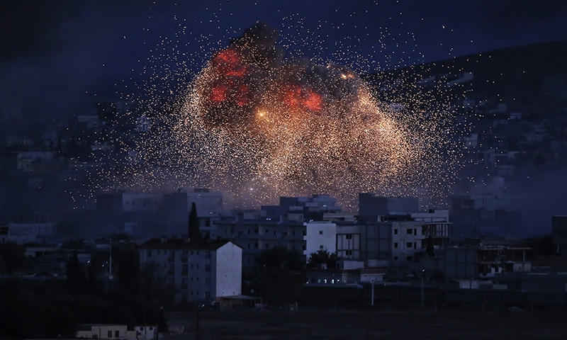 In this Oct 20, 2014 file photo, thick smoke and flames erupt from an airstrike by the US-led coalition in Kobani, Syria, as seen from a hilltop on the outskirts of Suruc, at the Turkey-Syria border.—AP/File
