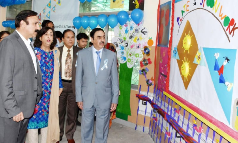 State Minister for CADD Dr Tariq Fazal Chaudhry looks at the art work by children in Islamabad on Tuesday. — INP