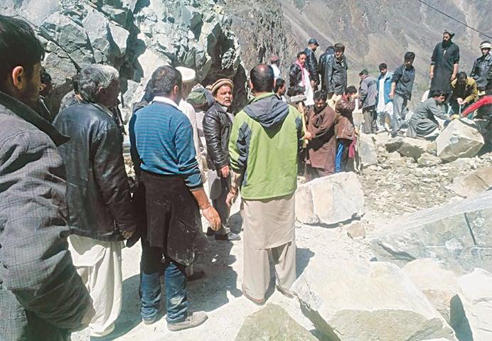 People clearing the Karakoram Highway blocked by landslides.—Dawn