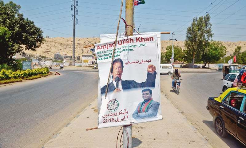 A banner featuring the photos of PTI chief Imran Khan and late-night defector Amjad Ullah Khan remains attached to a pole near the Shipowners College on Thursday.—White Star