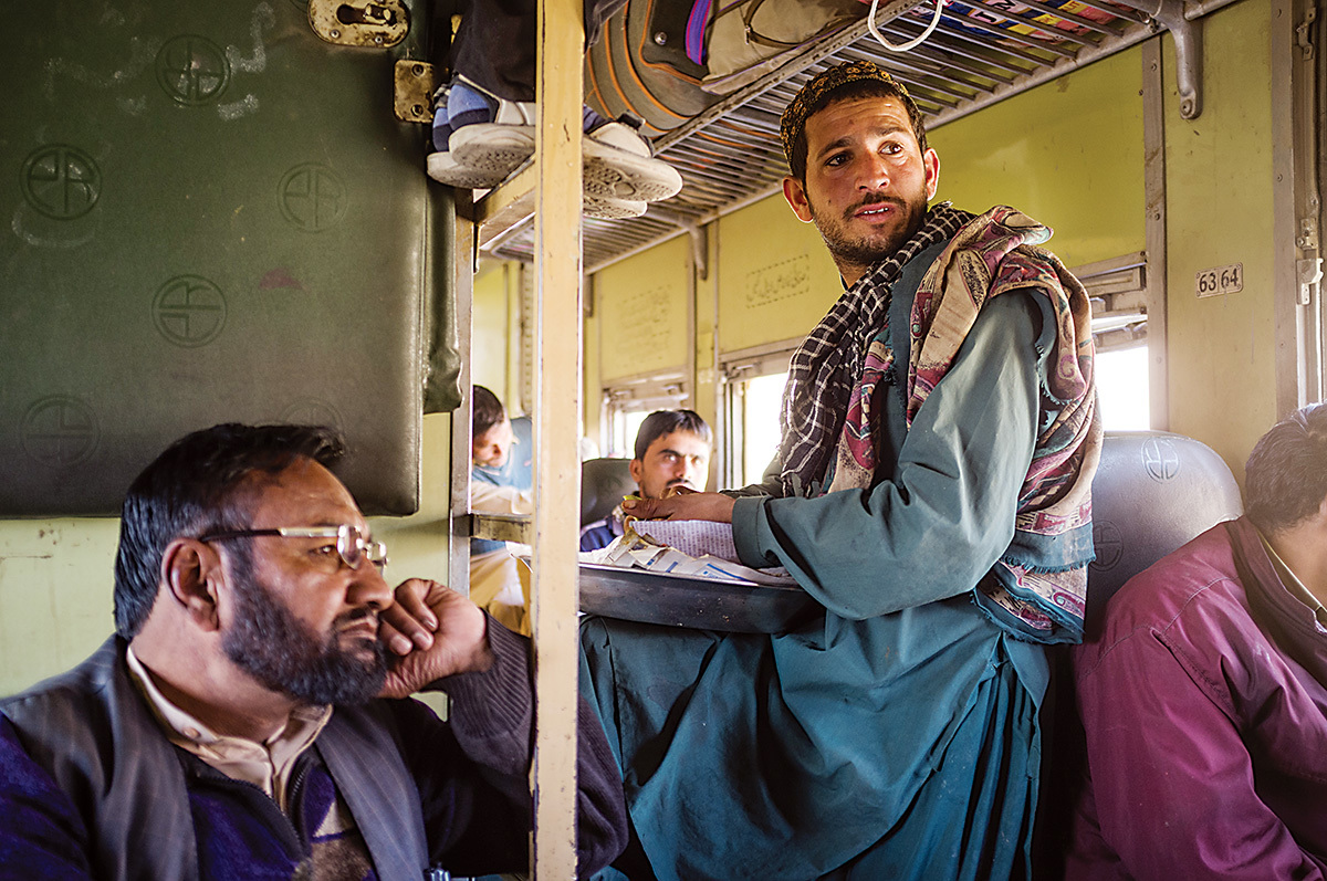 Gul Zadad , a passenger, looks out the window at the Sibi Junction, as a food vendor sells his wares