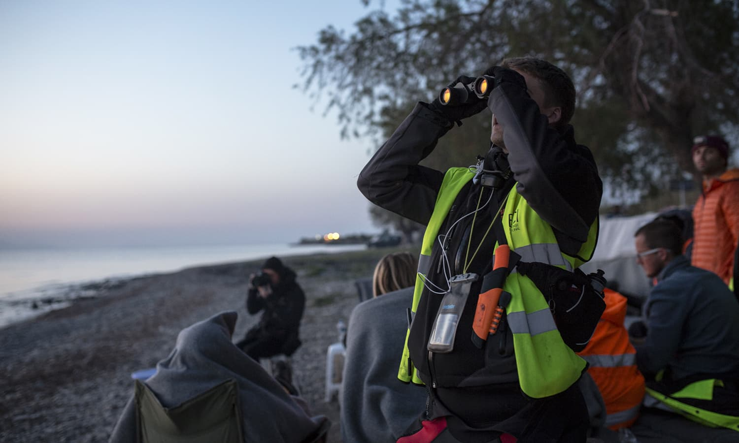 A European volunteer uses binoculars to look for migrants arriving by boat to the island of Lesbos in Greece. International volunteer teams have organised rescue mission, food distributions and all manner of aid for economic migrants arriving in Greece and along the Balkan route.
