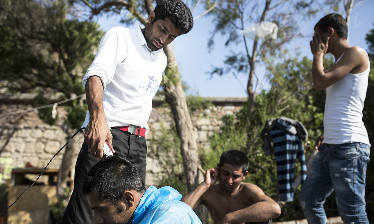 A young Pakistani man named Amer cut Abdil's hair at the No Borders Kitchen, an unlicensed camp run by European anarchists on the shore of Lesbos island in Greece.