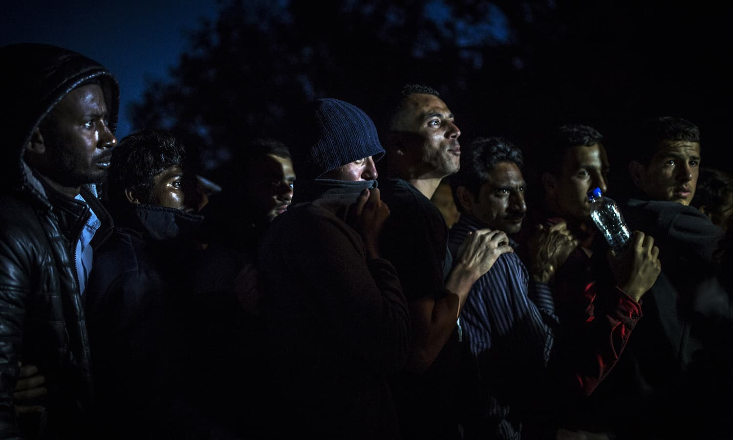Migrants, many of them Pakistani, line up for dinner at the No Borders camp on the island of Lesbos on April 7, 2016, which is run by volunteers. Although already warned they would be transferred to a detention center on the island, they've been granted a reprieve by the local mayor for an additional week.