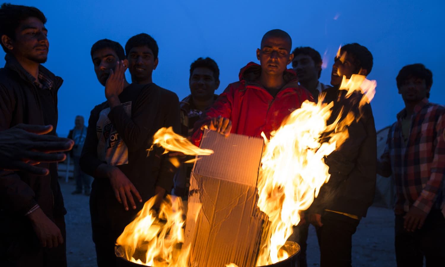 Pakistani men warm themselves by a fire in the evening at the No Borders Kitchen camp. The weather on the Greek island is hot during the day but drops significantly at night.