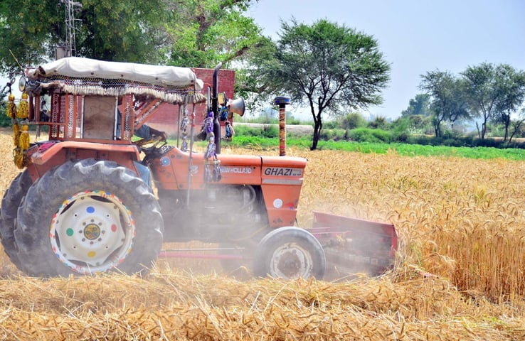 NAUDERO: A tractor thrashing wheat crop in a field on Monday. Combined tractor sales dipped in the first nine months of this fiscal year.—PPI