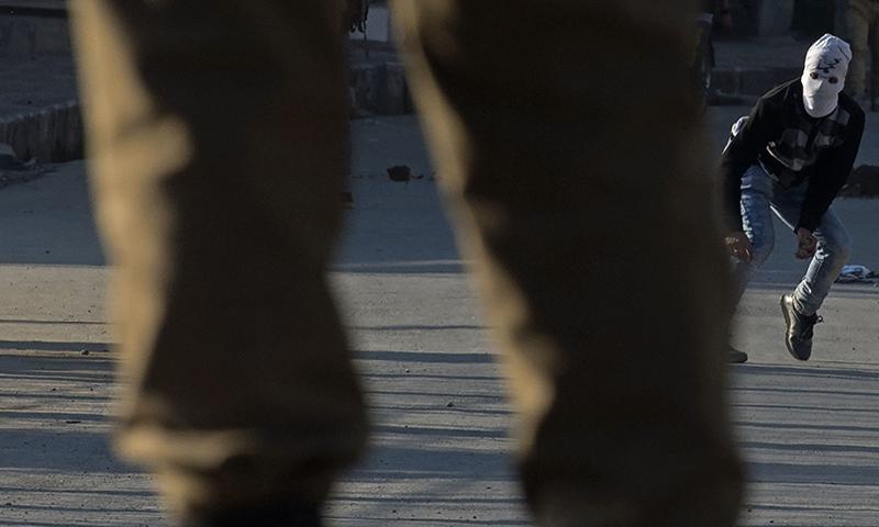 ایک کشمیری نوجوان ہندوستانی فوجیوں پر پتھراؤ کررہا ہے—اے ایف پی۔