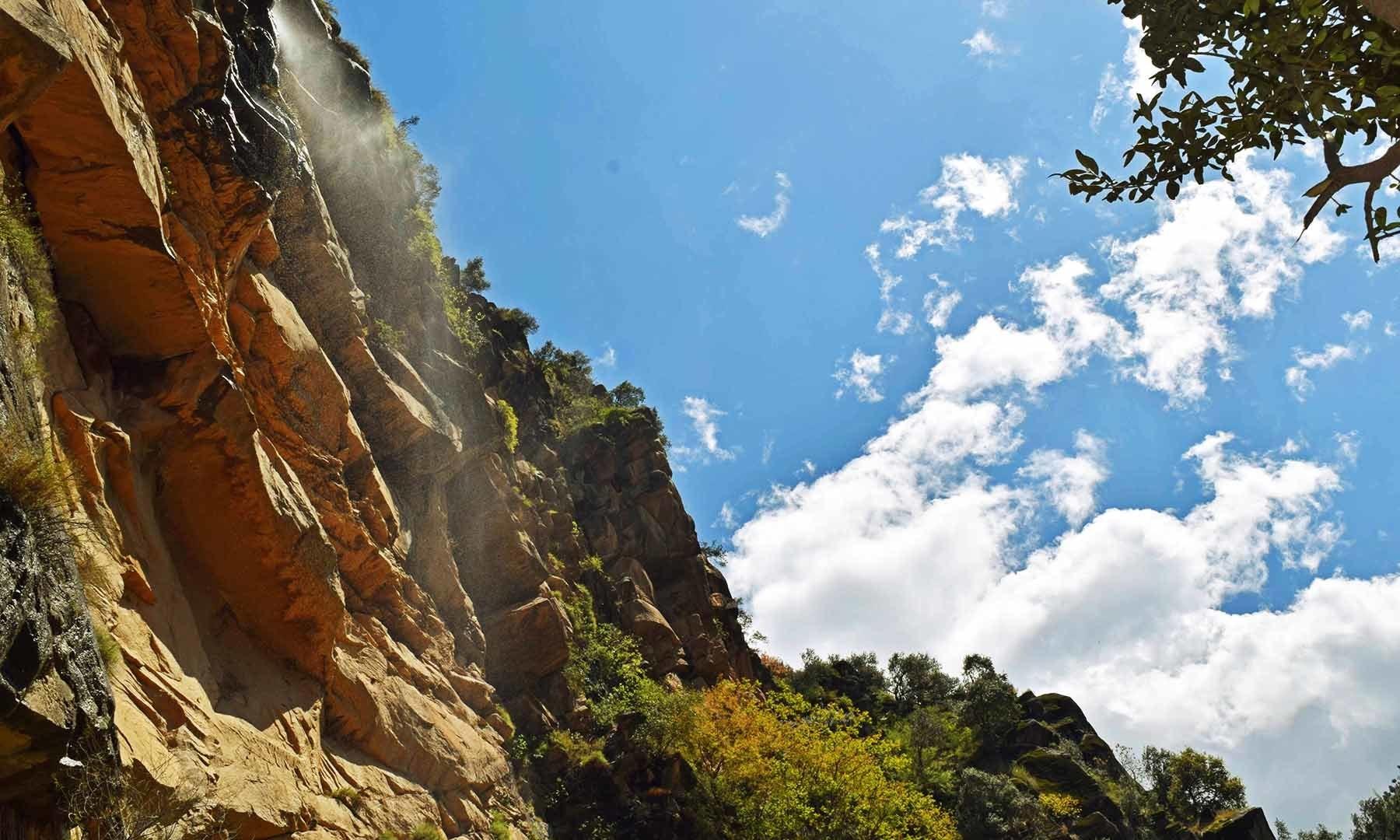 راستے میں پہاڑی سے پھوار کی شکل میں بہنے والا پانی، نیلا آسمان اور بادل۔— فوٹو امجد علی سحاب