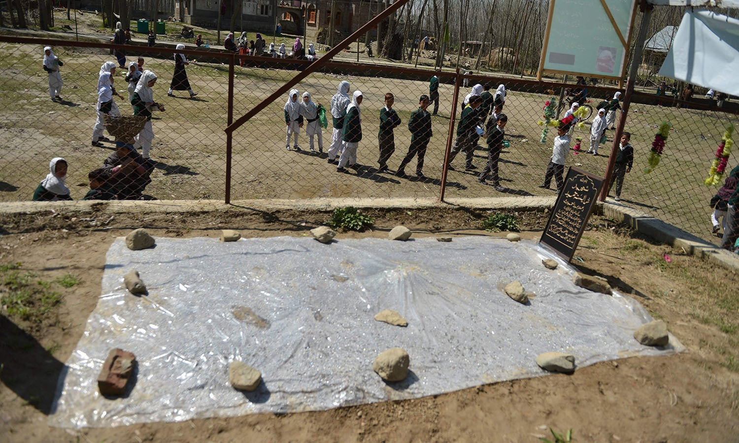 Kashmiri schoolchildren play near the grave of former pupil Shaista Hameed at Kakapora south of Srinagar.─AFP