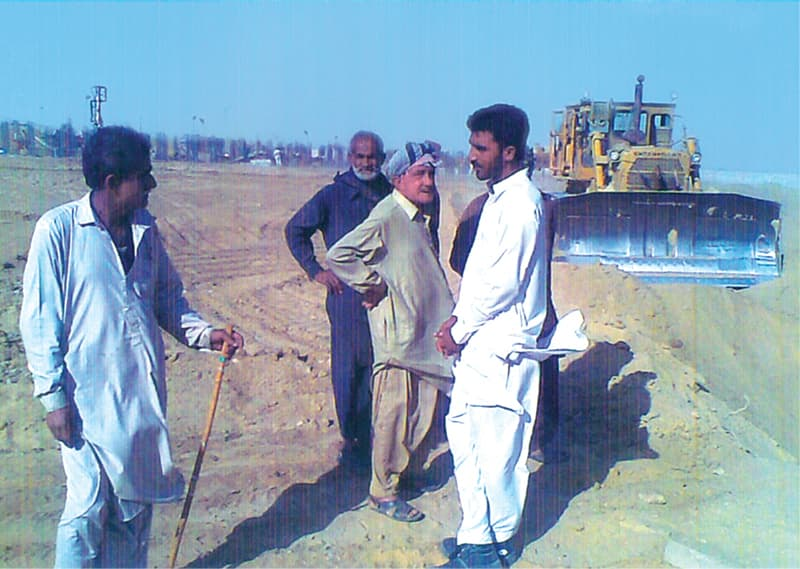Faiz Mohammed Gabol (third from left) watches as work proceeds on land where his orchards used to be.