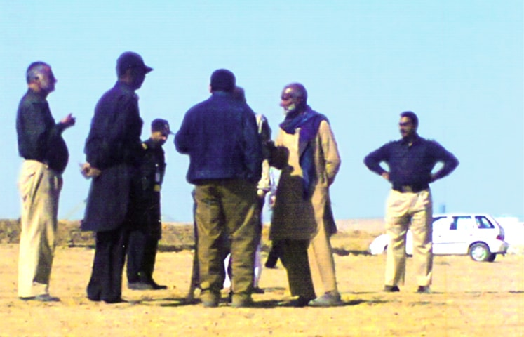 Police personnel oversee the beginning of construction work to counter resistance by villagers.
