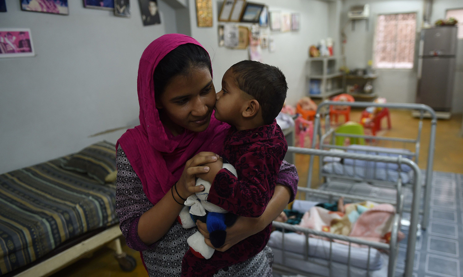 A staff member plays with an abandoned child at a welfare office of the Edhi Foundation in Karachi.    – AFP