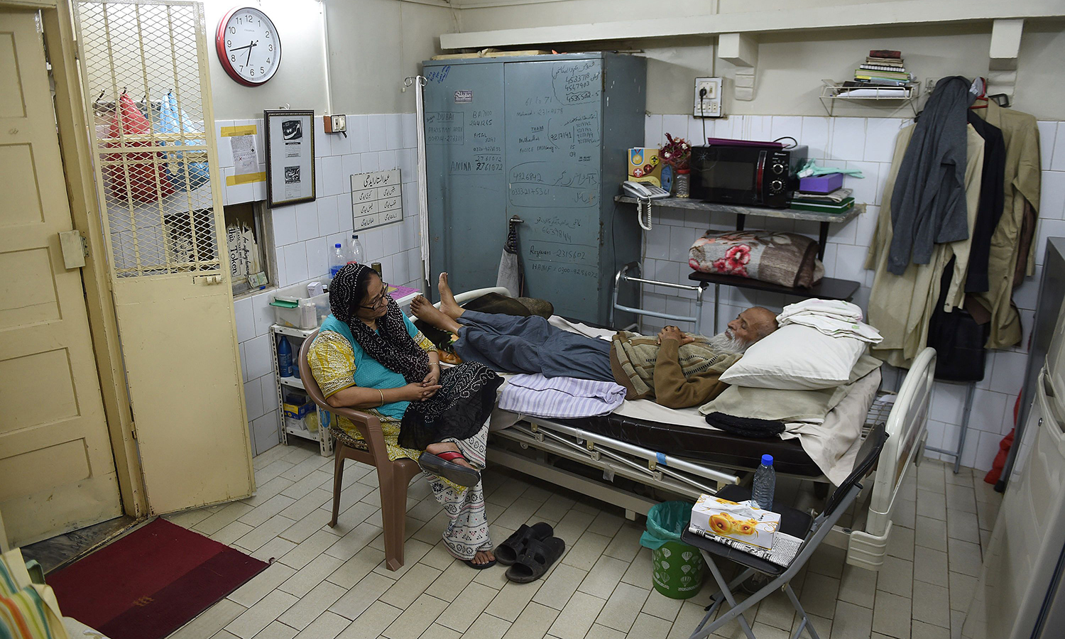 Abdul Sattar Edhi speaks with his wife Bilquis Edhi in his office in Karachi. —AFP