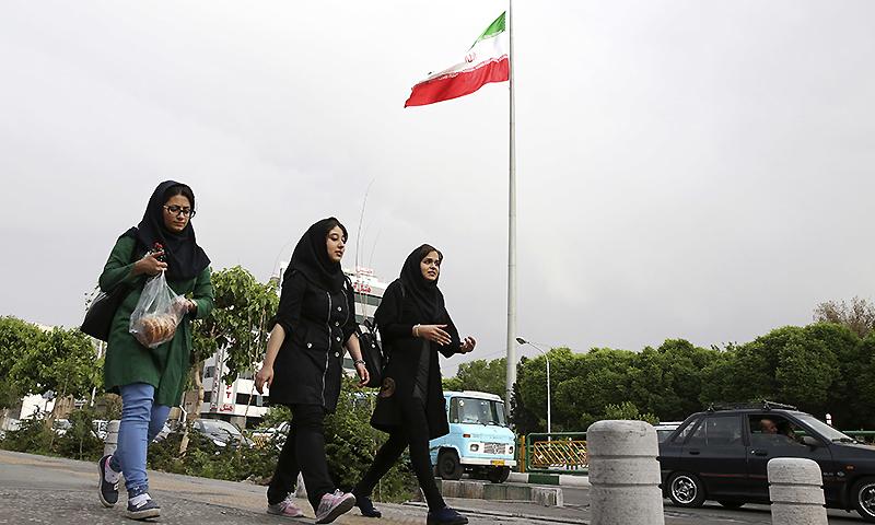 Iranian women make their way down a sidewalk in downtown Tehran, Iran. ─ AP